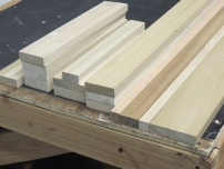 Cut lumber for bed headboard and passenger side upper cabinet