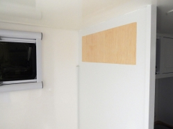 Prepped, bonded, and screwed overbed cabinets on rear bed walls