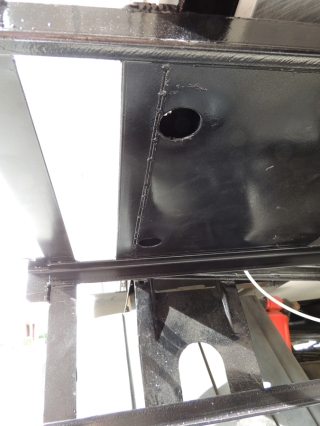 Drilled bolt access holes in driver side under subframe storage box heat shield