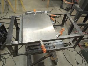 Welded steel heater exhaust heat shield to driver side under subframe storage box mount